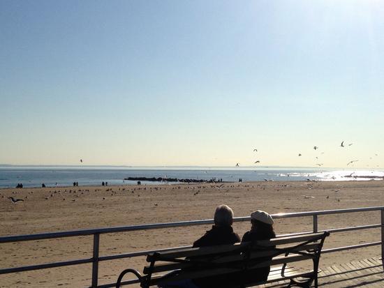 Coney Island im Winter: Möwen, Mützen, Bank und Strand