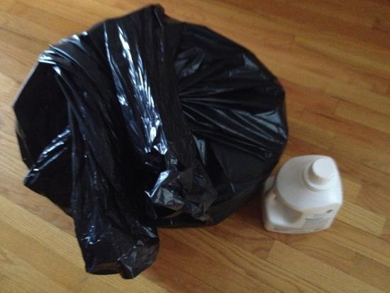 Mülltüte mit Wäsche und Waschmittel